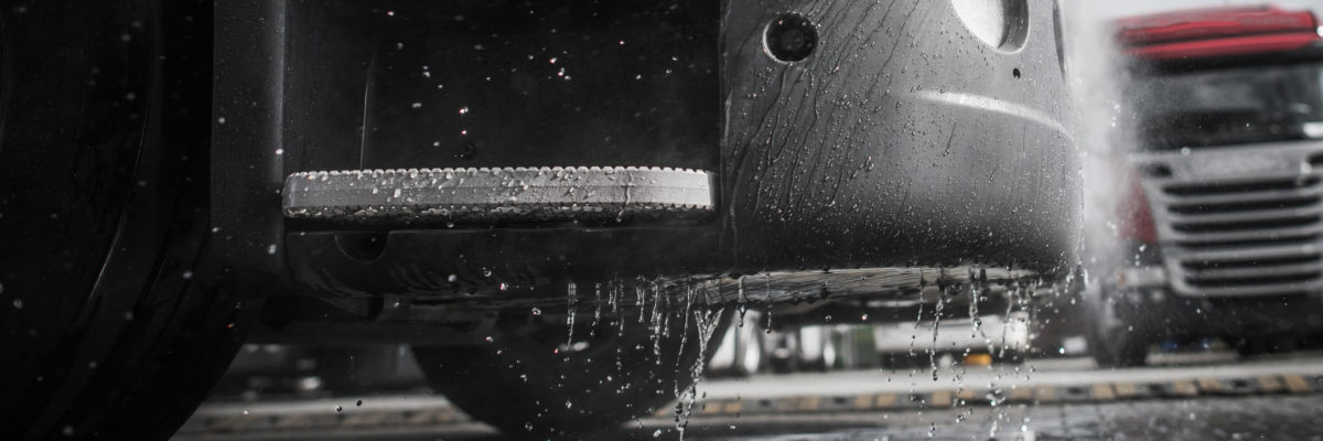 Pressure Washing Semi Truck Closeup Photo. Wet Tractor Bumper. Clean Vehicle Concept Photo.
